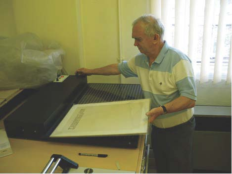 Collection Care Volunteer Tom Bowman encapsulating board in archival polyester